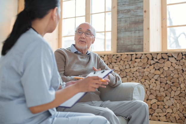 My complaints. doctor holding clipboard while taking notes and talking to experienced smart senior man