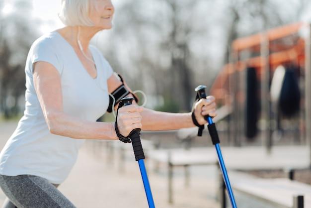 Мои костыли. счастливая белокурая женщина улыбается и использует костыли во время тренировки