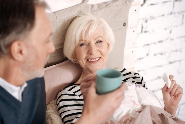 Моя дорогая. улыбающаяся старшая женщина собирается выпить горячего напитка от любящего мужа.