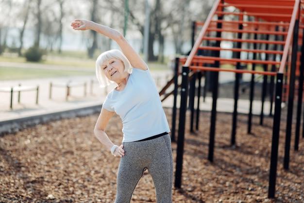 私の一日。スポーツウェアを着て野外で運動するあふれんばかりの老婆