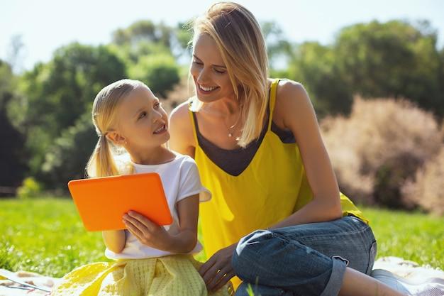 내 사랑하는 소녀. 태블릿을 들고 야외에서 그녀의 엄마와 이야기하는 사랑스러운 어린 소녀