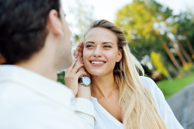 親愛なる君へ。彼女の頬に触れながら彼の妻を見ている素敵な若い男