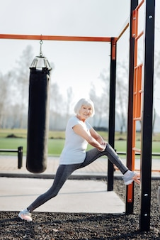 私の決意。スポーツ服を着て野外で運動する陽気なブロンドの女性