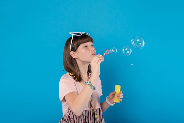 My entertainment. joyful lovely girl wearing stylish clothes and blowing soap bubbles