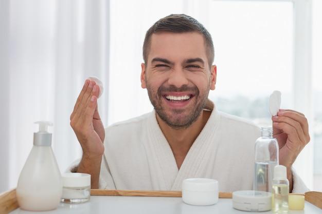 私の顔。綿のパッドを手に持って鏡を見ている幸せな陽気な男