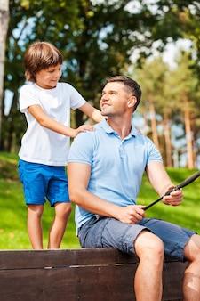 Мой отец лучший! счастливый отец и сын вместе ловят рыбу, сидя на набережной