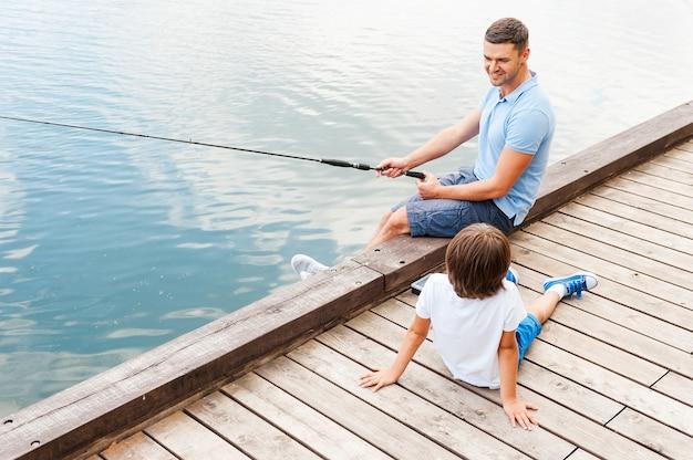 Мой отец лучший на рыбалке. вид сверху веселых отца и сына, вместе ловящих рыбу, сидя на берегу реки