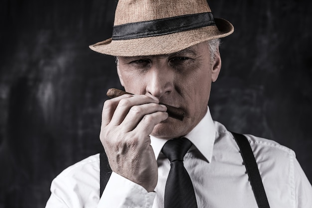 My favorite cigar. confident senior man in hat and suspenders smelling cigar while standing against dark background