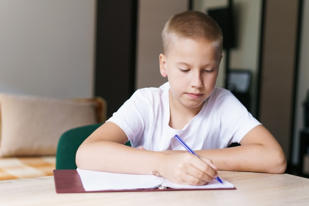 私のお気に入りの主題ハンサムな笑顔のブロンドの男の子は座っている間彼のノートに働いて書いています