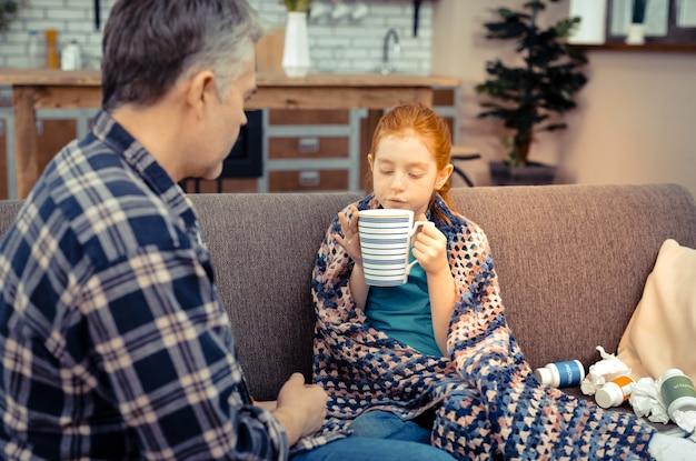 私の好きな飲み物。父親と一緒にソファに座ってティーカップを持っている素敵な楽しい女の子