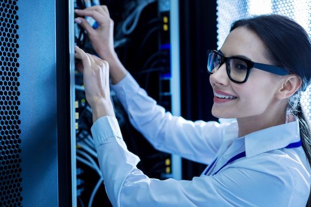 Моя любимая работа. буйная умная женщина работает в сервисном шкафу и ремонтирует провода