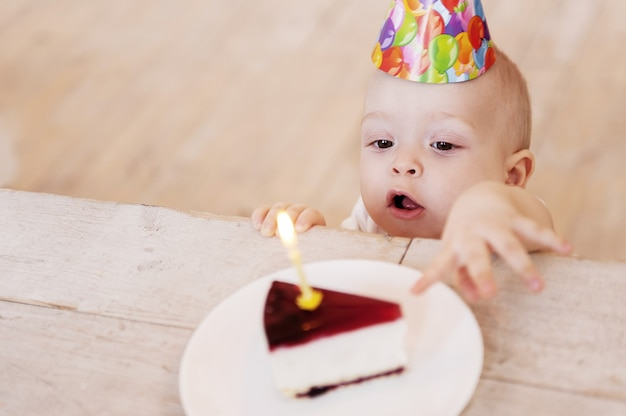 My first birthday cake! top view of cute little baby in party hat stretching hand to the plate with cake and keeping mouth open