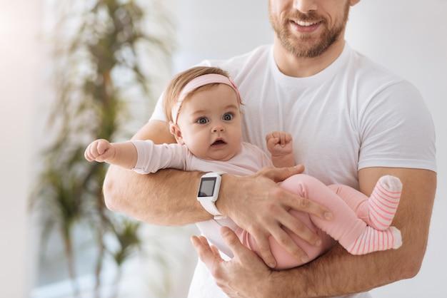 내 인생 첫해. 젊은 아버지의 손에 누워 관심과 긍정적 인 감정을 표현하면서 멀리 보는 귀여운 작은 관련 아기