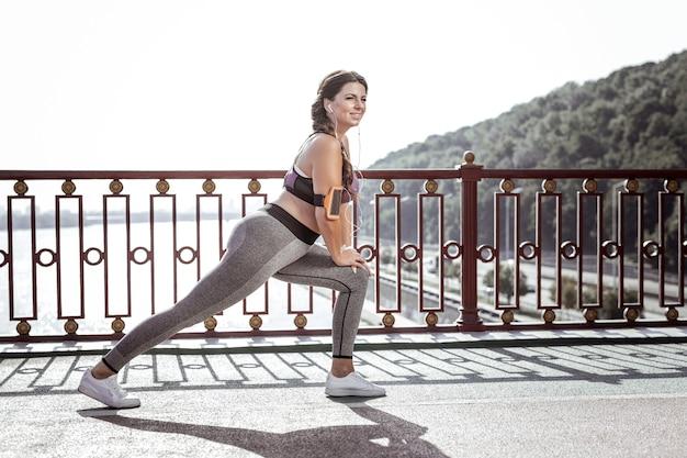 私の柔軟性。ストレッチ運動をしながら笑顔の楽しい若い女性
