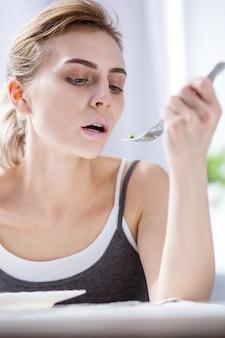 私の食べ物。エンドウ豆を見ながらテーブルに座っている元気のない若い女性