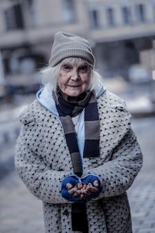 내 음식. 소수의 과자를 들고 당신에게 웃는 긍정적 인 가난한 여자