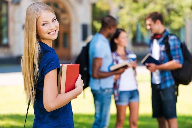 私の未来は私の手にあります。本を持って、大学の建物の近くに立って、バックグラウンドでチャットしている彼女の友人と笑顔の美しい若い女性