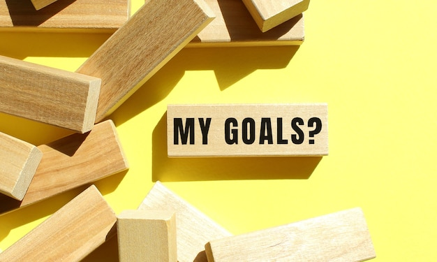 My goals text written on a wooden blocks on a yellow background.