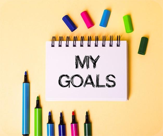 멀티 컬러 마커 근처의 베이지 색 표면에 흰색 노트에 기록 된 내 목표