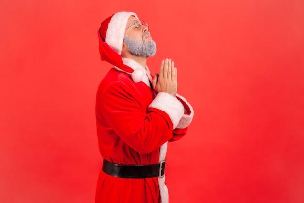 맙소사 도와주세요. 걱정스러운 얼굴로 올려다보며 기도하는 산타클로스.