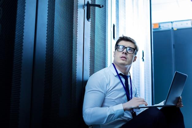Моя хорошая работа. решительный серьезный мужчина сидит на полу и работает на своем ноутбуке