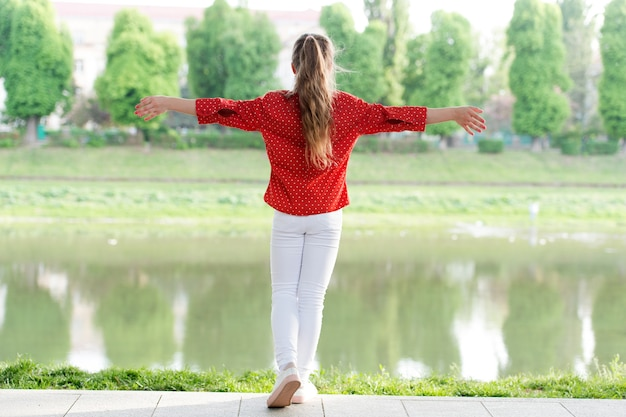 Моя прическа говорит сама за себя. маленькая девочка с длинной прической в повседневной одежде на берегу реки. прелестный маленький ребенок нося прическу