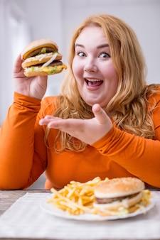 私の幸せ。テーブルに座ってフライドポテトとサンドイッチを食べる意志の弱い幸せな太りすぎの女性