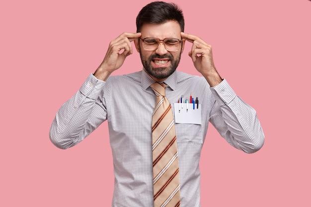 La mia testa impazzisce. l'uomo barbuto scontento tiene le dita anteriori sulle tempie, sente pressione e angoscia, stringe i denti per un terribile mal di testa