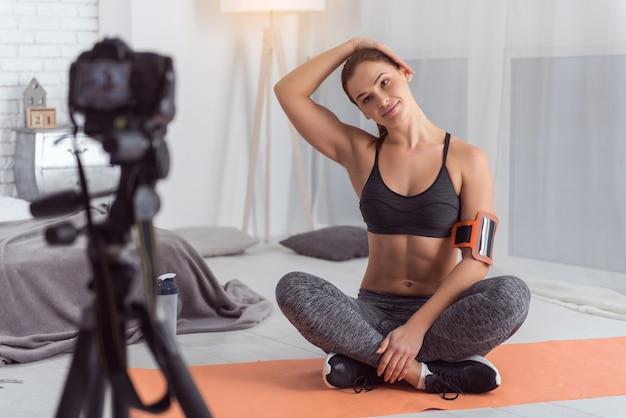 私の健康的なライフスタイル。魅力的な陽気なアスレチック黒髪のブロガーは、カーペットの上に座って彼女のブログのビデオを作成しながら、笑顔でエクササイズをしています
