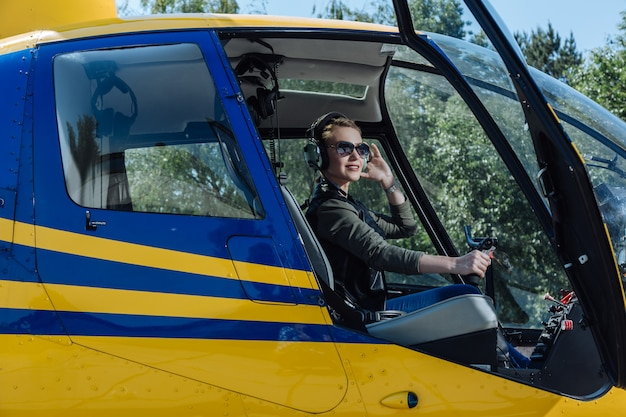 My hobby. beautiful female pilot sitting in a helicopter and posing for the camera while smiling elatedly
