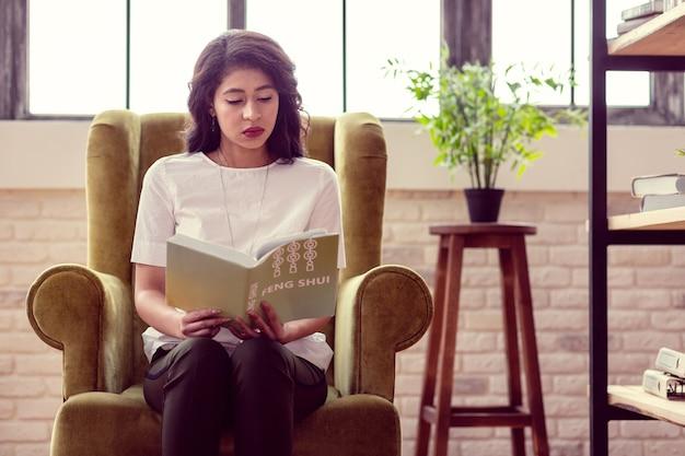 Мое хобби. милая умная женщина читает книгу о фэн-шуй, сидя в кресле