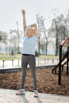 私のインスピレーション。スポーツ服を着て野外で運動している金髪の女性の笑顔
