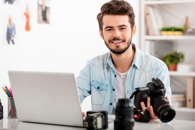 私の仕事は私の情熱です。カメラを持って、彼の職場に座って笑っているハンサムな若い男