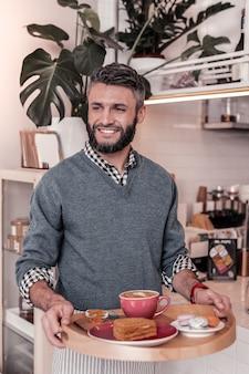 私の仕事。カフェでウェイターとして働いている間、食べ物のトレイを持っている前向きなうれしそうな男