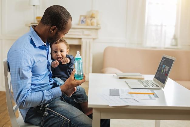 私の子供。彼のラップトップでテーブルに座っている間彼の幼い息子と彼のボトルを保持している献身的な愛情のある若いアフリカ系アメリカ人のお父さん