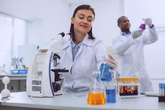내 실험실. 튜브와 백그라운드에서 서있는 그녀의 동료와 함께 일하는 쾌활한 숙련 된 과학자