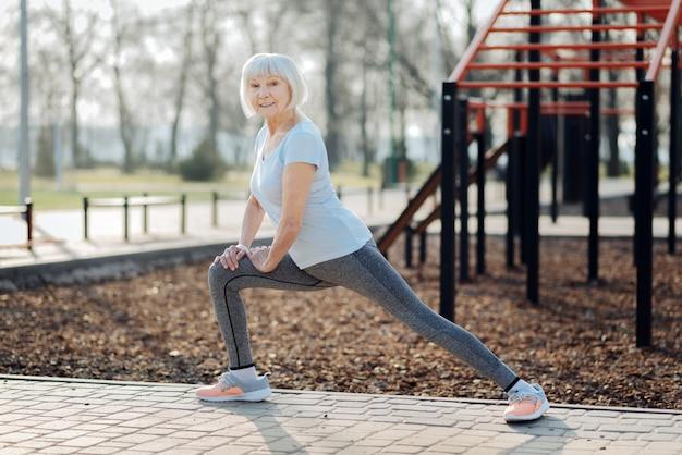 私のライフスタイル。スポーツ服を着て野外で運動するインスピレーションを得た年配の女性