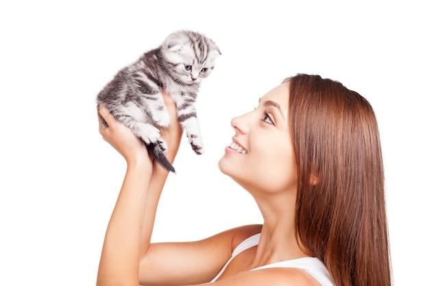 Мой маленький пушистый друг. красивая молодая женщина, держащая маленького котенка в руках и смотрящая на него с улыбкой, стоя изолированной на белом фоне