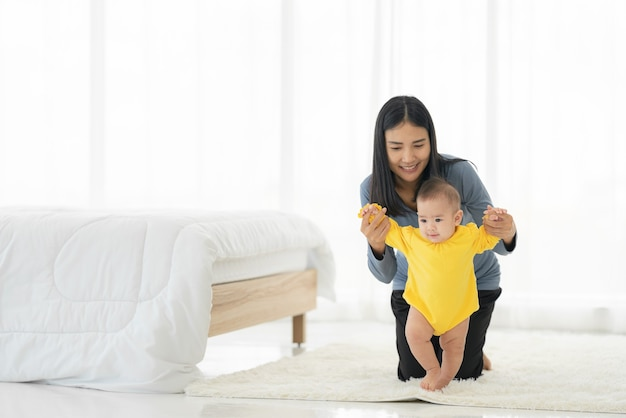 私の小さな女の子は最初の一歩を踏み出します。家族の幸せな小さな赤ちゃんが母親と一緒に歩くことを学ぶ