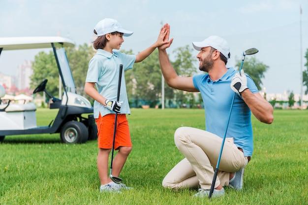 私の小さな勝者!ゴルフ場に立ってハイタッチをする元気な青年と息子