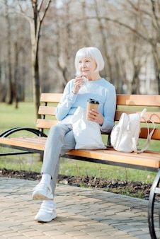 My lunch. alert old woman enjoying her coffee and a cookie while sitting on the bench
