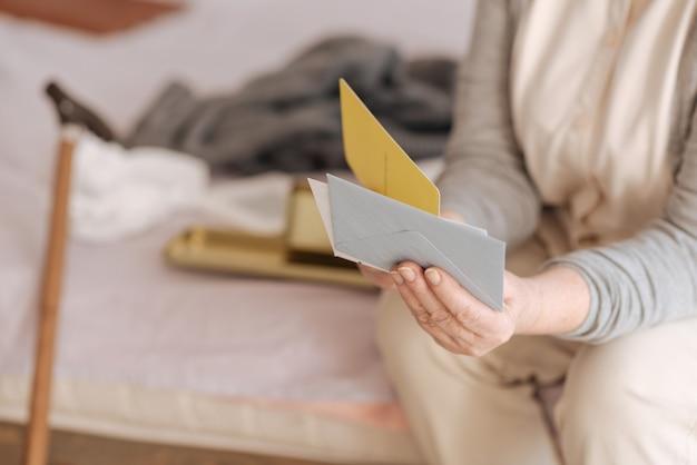 내 메일. 침대에 앉아있는 동안 좋은 유쾌한 세 여성이 봉투를 닫습니다.