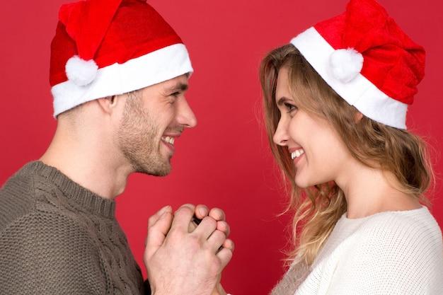 私の主なプレゼント。冬の服を着て、お互いを見て手をつないでサンタの帽子をかぶっているゴージャスな若いクリスマスのカップル