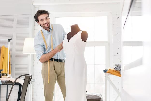 내 걸작. 그의 사무실에서 일하고 새 드레스를 만드는 집중된 젊은 재단사
