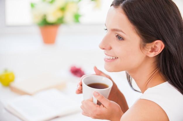 私の朝のコーヒー。ベッドに座って、毛布で覆われている間カップを保持している若い笑顔の女性の側面図