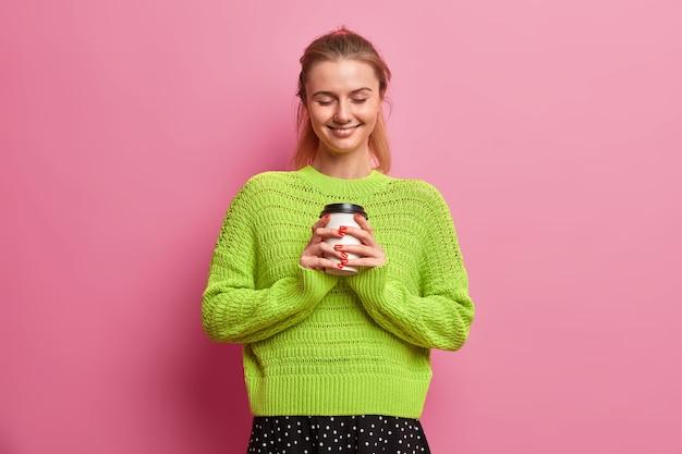 내 아침은 커피에서 시작됩니다. 행복한 긍정적 인 유럽 여자는 맛있는 음료의 일회용 컵을 들고 행복하게 미소 짓고 눈을 감고 서서 즐거운 것을 상상합니다.