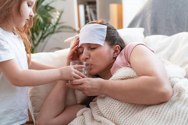 母は病気です。病気の母親にガラスの水をもたらす小さな娘。