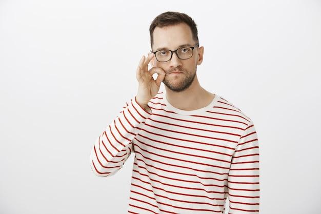 私の口は要塞です。メガネ、手でジェスチャーを作る、唇をジッパーで深刻な面白い白人男性の肖像画