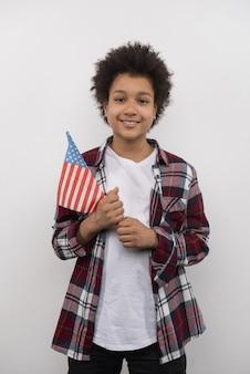 Моя нация. радостный позитивный мальчик, стоящий с флагом сша, глядя на вас