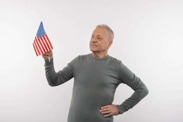 Моя национальность. радостный старший мужчина улыбается, держа флаг сша